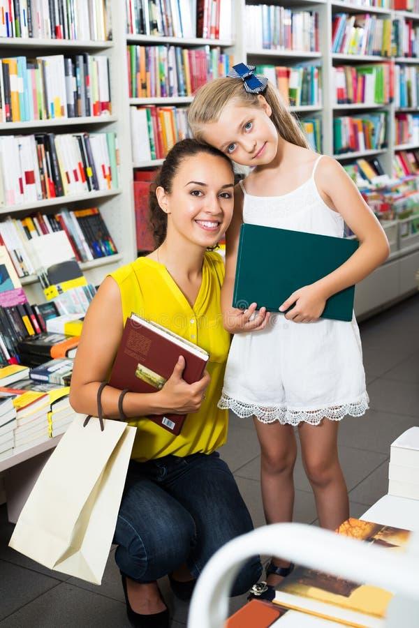 Vrouw met meisje het kopen boeken stock afbeelding