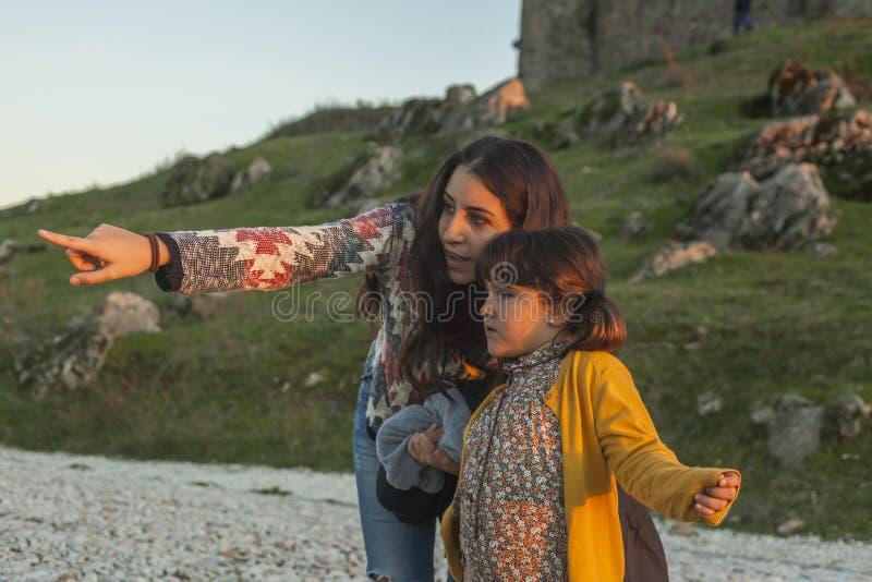 Vrouw met meisje het richten op één of andere plaats in een aard landsc royalty-vrije stock afbeeldingen