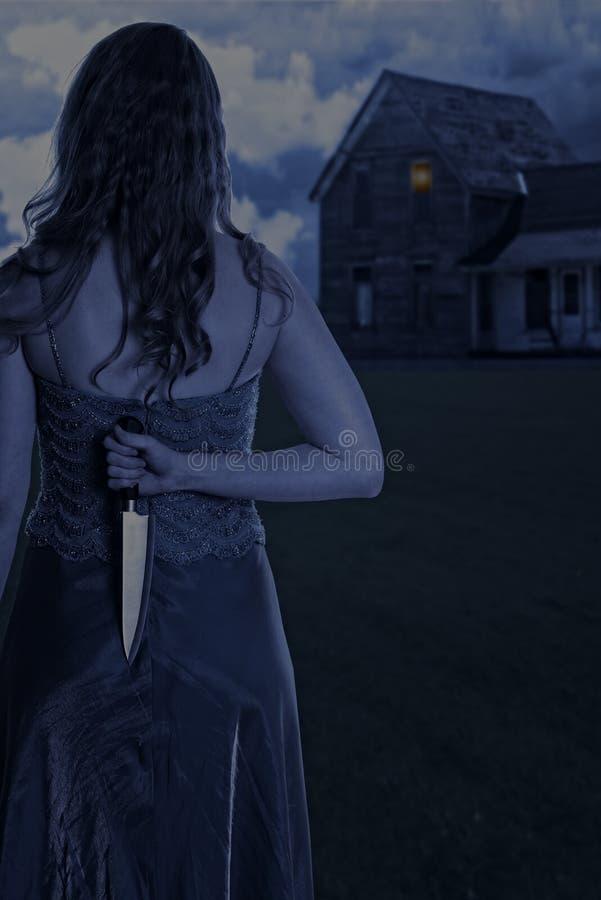 Vrouw met mes buiten huis bij nacht royalty-vrije stock foto's