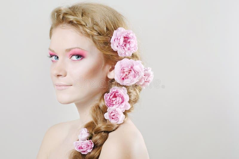 Vrouw met met bloemen en rozen in haar stock foto