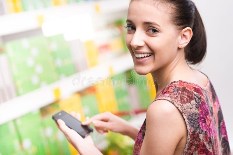 Vrouw met mobiel bij supermarkt stock afbeelding