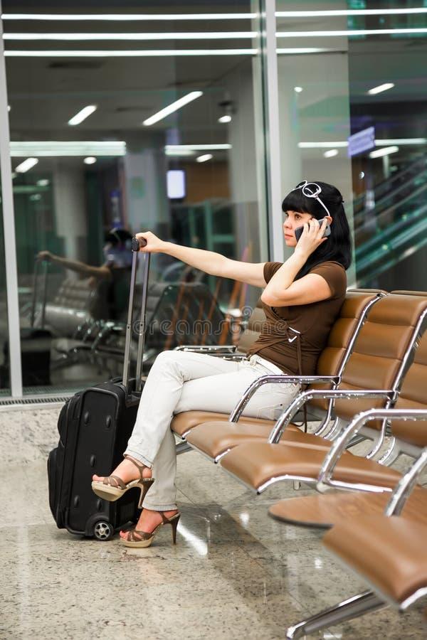 Vrouw met mobiele telefoon in de luchthaven royalty-vrije stock foto's