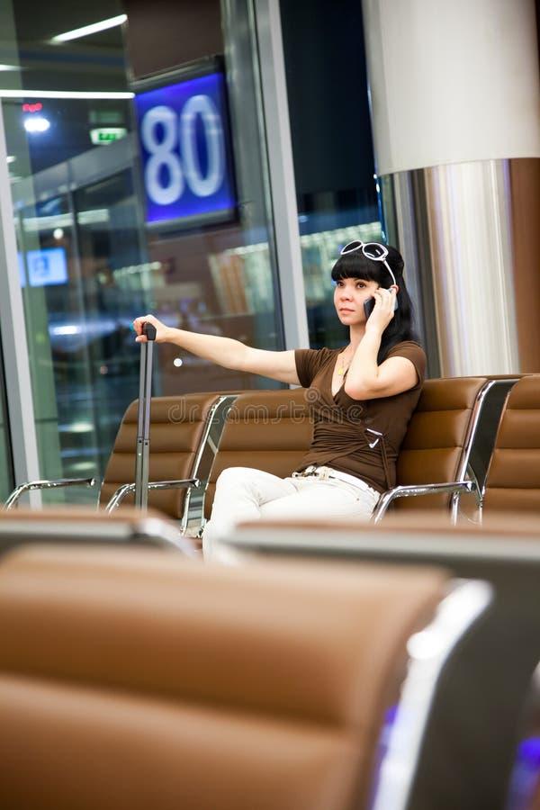 Vrouw met mobiele telefoon in de luchthaven royalty-vrije stock foto