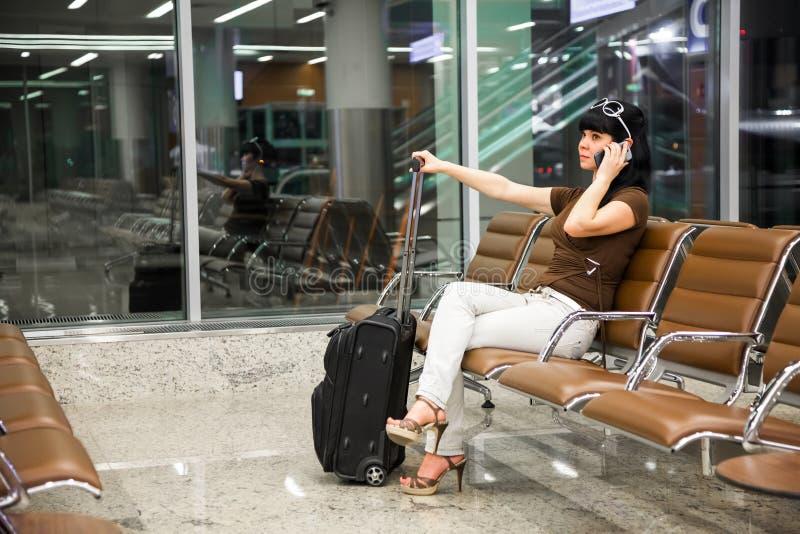 Vrouw met mobiele telefoon in de luchthaven stock afbeelding