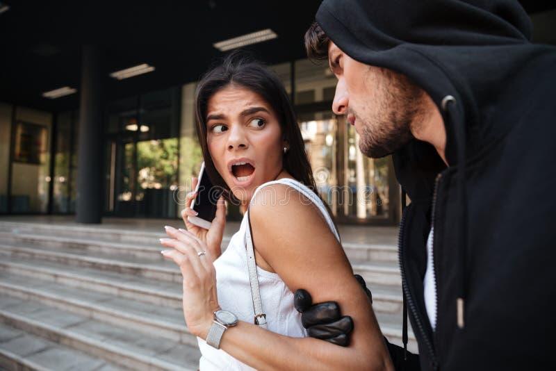 Vrouw met mobiele telefoon die door de misdadige mens schreeuwen en wordt aangevallen stock afbeeldingen