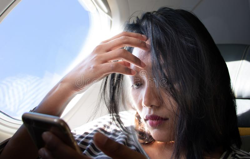 Vrouw met mobiele telefoon die door vliegtuig reizen royalty-vrije stock afbeeldingen