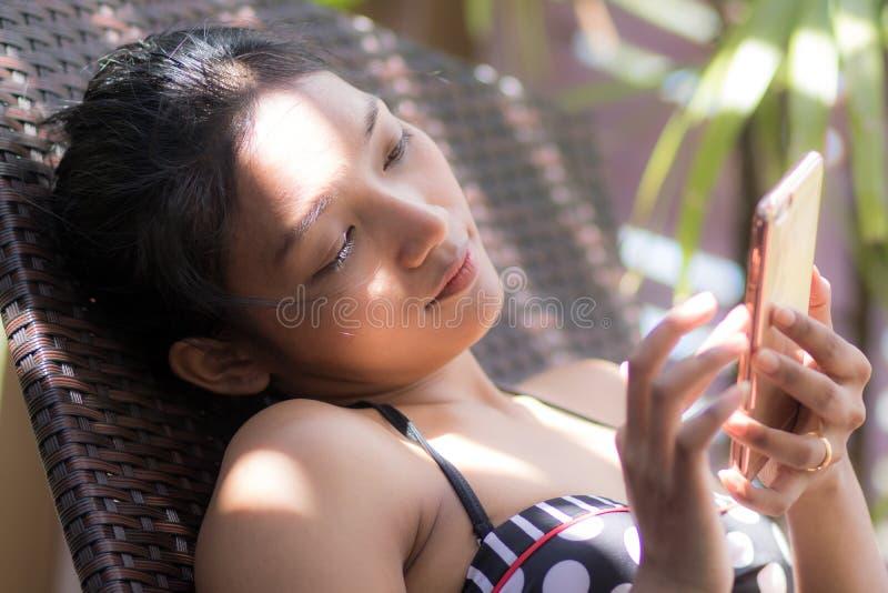 Vrouw met mobiele telefoon die op lanterfanter zonnebaden stock foto's