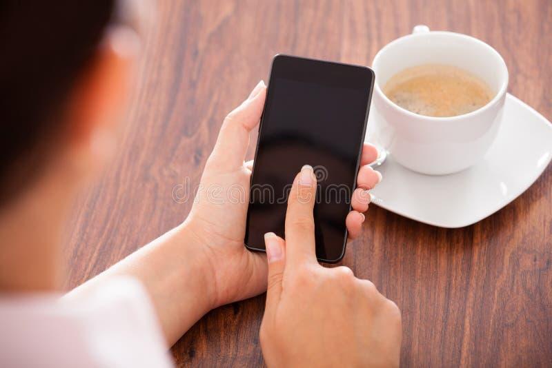 Vrouw met mobiele telefoon en kop stock foto