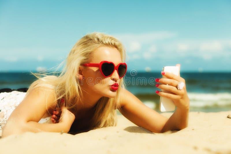 Vrouw met mobiele telefoon op strand stock afbeelding