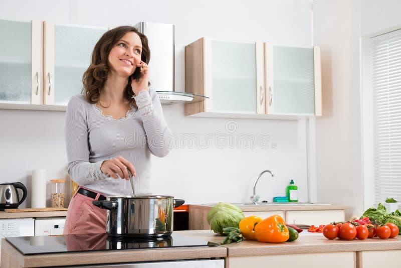 Vrouw met Mobiele Telefoon terwijl het Koken stock foto's