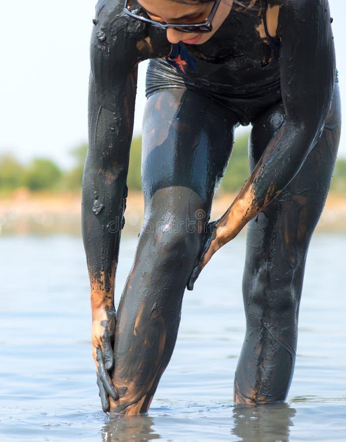 Vrouw met modder bij zout meer wordt gesmeerd dat stock foto's