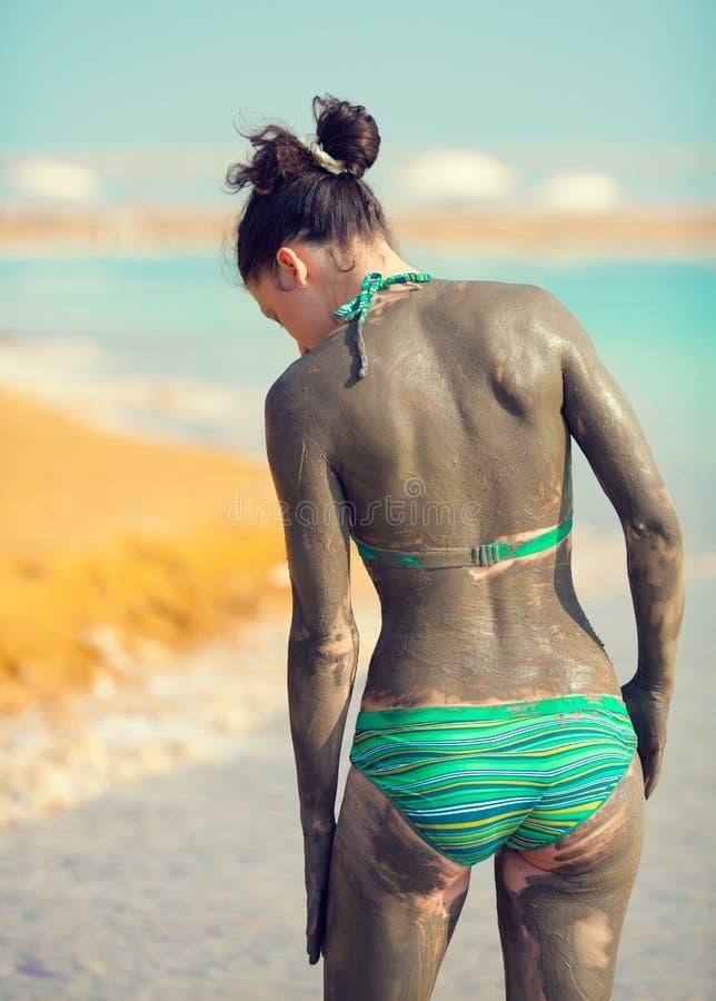 Vrouw met moddermasker dat wordt gesmeerd stock afbeelding