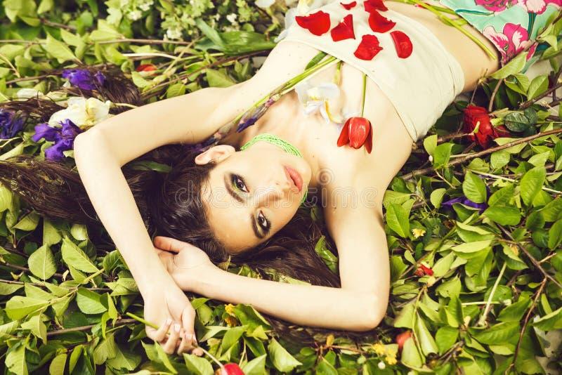 vrouw met modieuze make-up met bloemen op groene bladeren royalty-vrije stock afbeelding