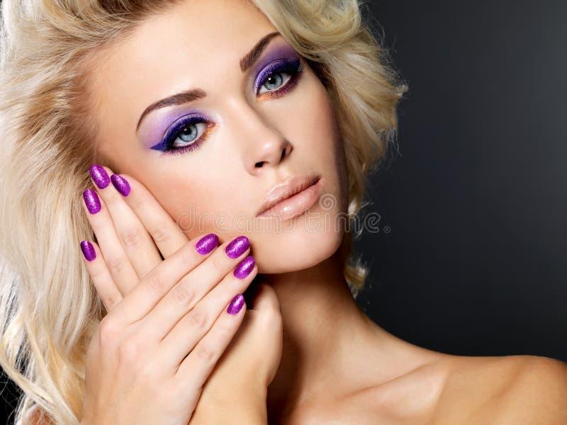 Vrouw met mooie purpere manicure stock afbeeldingen