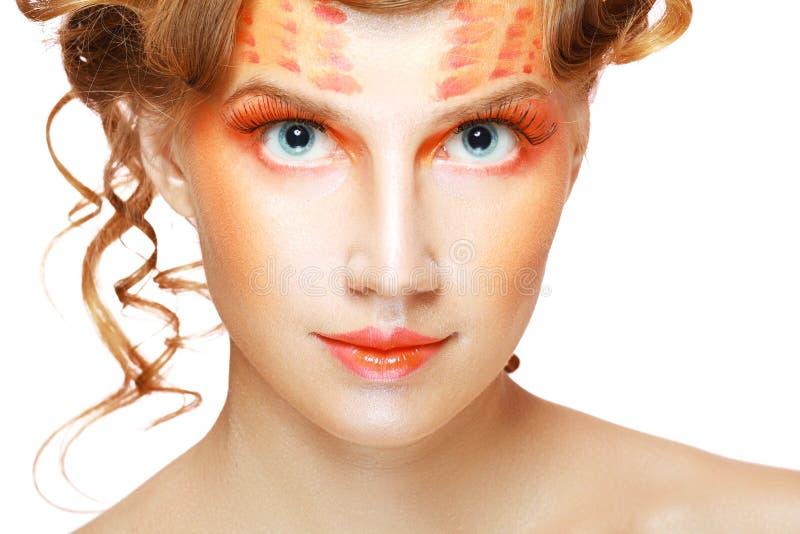 Vrouw met oranje artistiek gezicht stock afbeelding