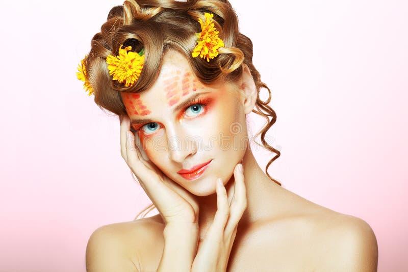 Vrouw met oranje artistiek gezicht stock afbeeldingen