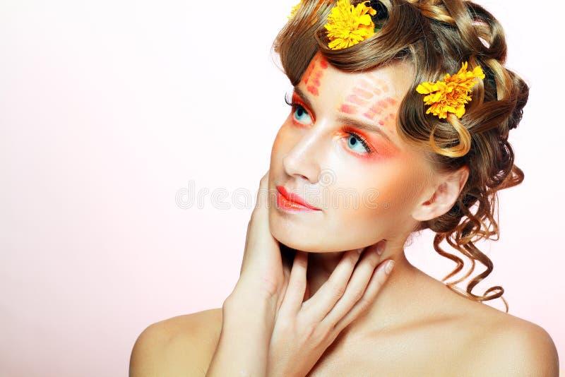 Vrouw met oranje artistiek gezicht stock fotografie