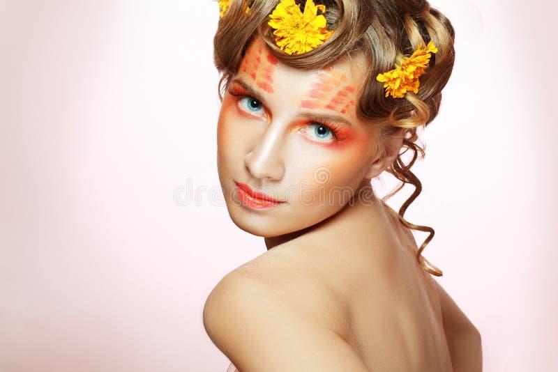 Vrouw met oranje artistiek gezicht royalty-vrije stock afbeelding