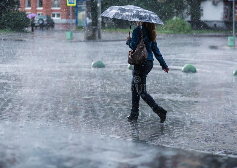 Vrouw met paraplu die op straat tijdens zware regen gaan stock foto
