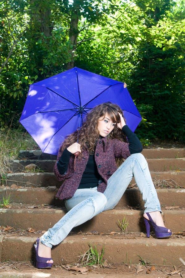 Vrouw met paraplu in een park in daling stock foto's