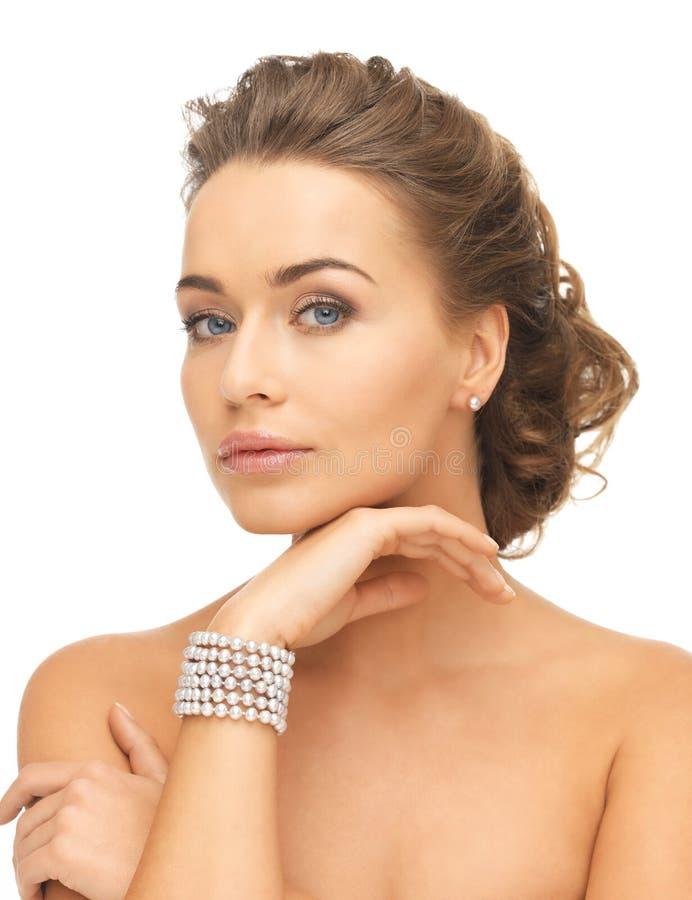 Vrouw met pareloorringen en armband royalty-vrije stock afbeelding