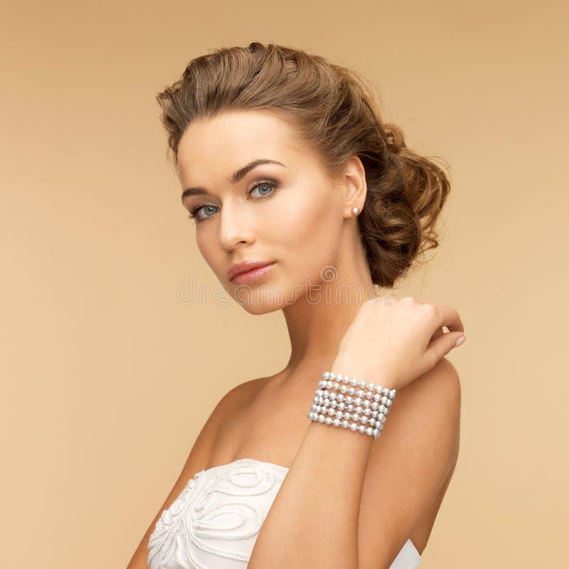 Vrouw met pareloorringen en armband stock afbeelding
