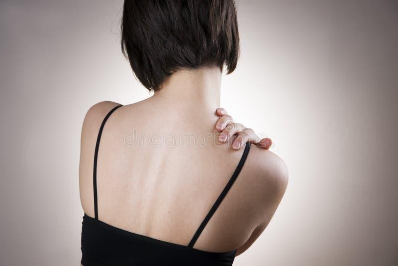 Vrouw met pijn in schouder Pijn in het menselijke lichaam stock afbeelding