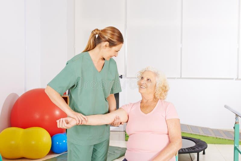Vrouw met pijnlijke schouder in fysieke therapie royalty-vrije stock afbeelding