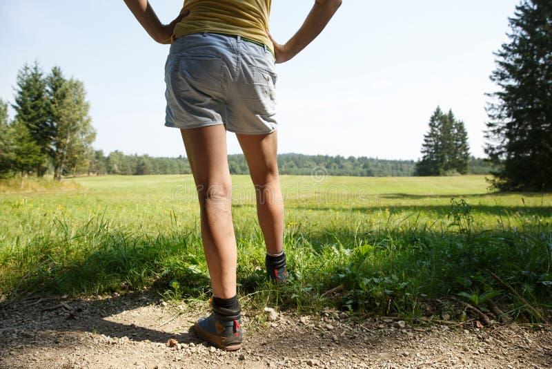 Vrouw met pijnlijke spataders op benen die op een gang door aard rusten stock fotografie