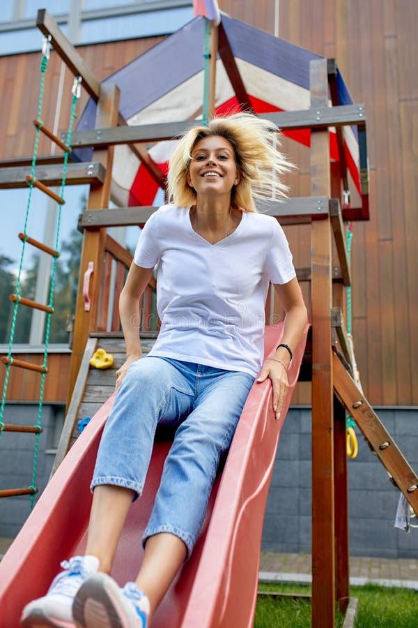 Vrouw met plezier op een kinderdia Kindertijd eindigt niet alle leven, volwassenen als kinderen Levensstijl ontwerpen royalty-vrije stock afbeelding