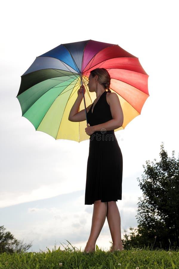 Vrouw met regenboogparaplu op een heuvel stock afbeeldingen