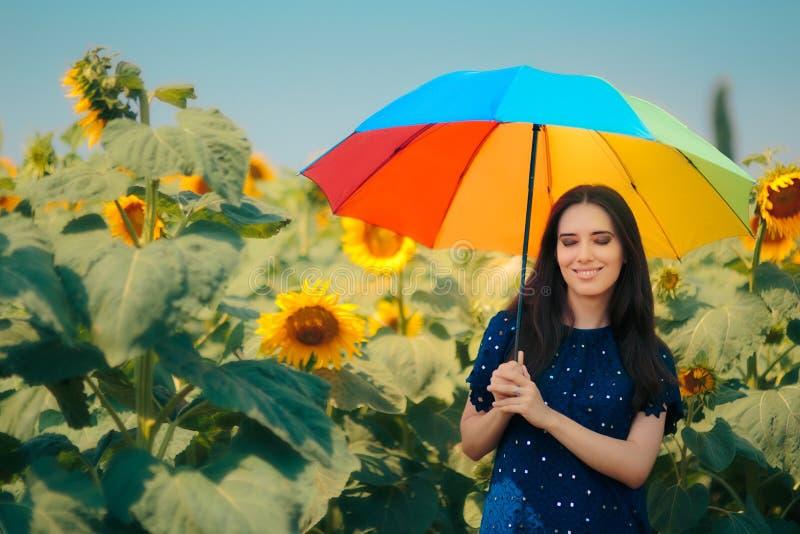 Vrouw met Regenboogparaplu op het Gebied van de de Zomerzonnebloem royalty-vrije stock fotografie