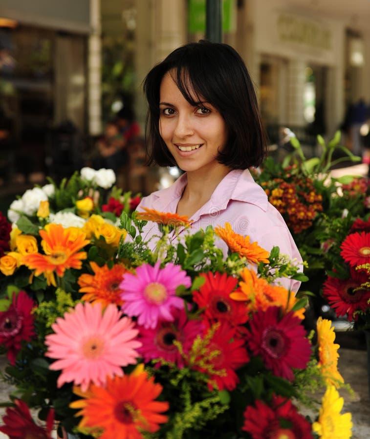 Vrouw met reusachtig boeket van bloemen in openlucht stock afbeeldingen