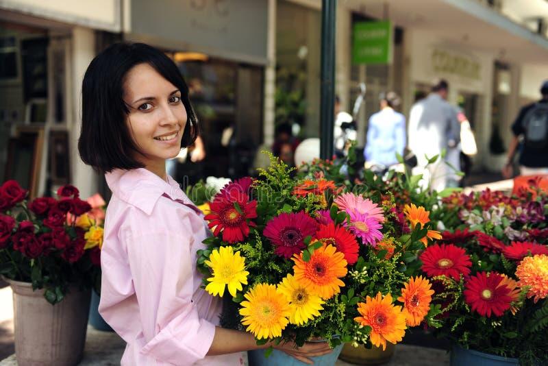 Vrouw met reusachtig boeket van bloemen in openlucht stock afbeelding