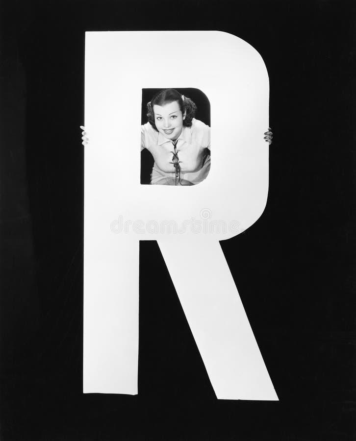 Vrouw met reusachtige brief R (Alle afgeschilderde personen leven niet langer en geen landgoed bestaat Leveranciersgaranties dat  royalty-vrije stock fotografie