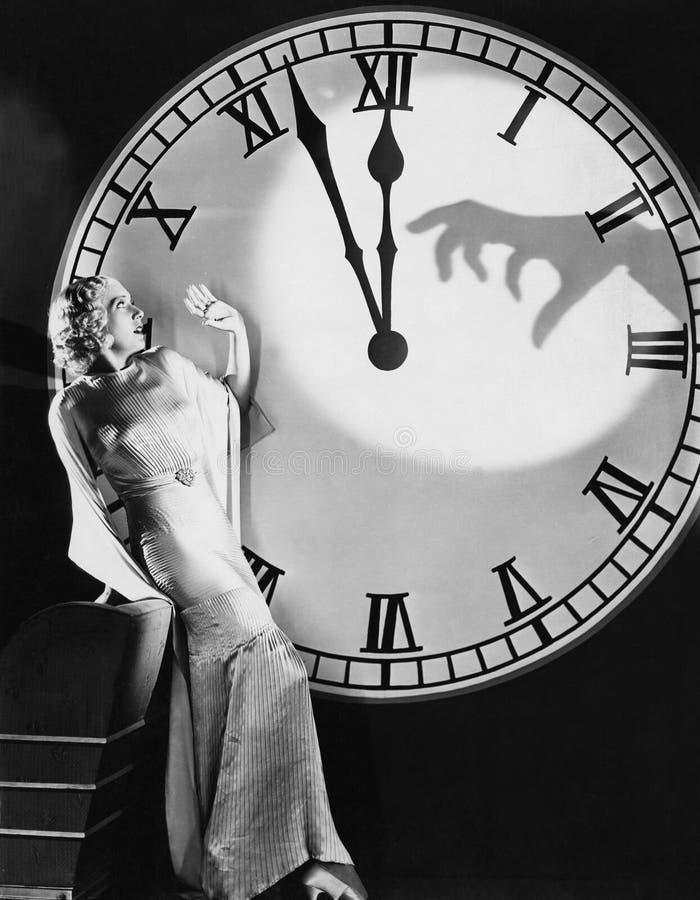 Vrouw met reusachtige klok die van het bang maken van hand terugdeinzen (Alle afgeschilderde personen leven niet langer en geen l stock foto's