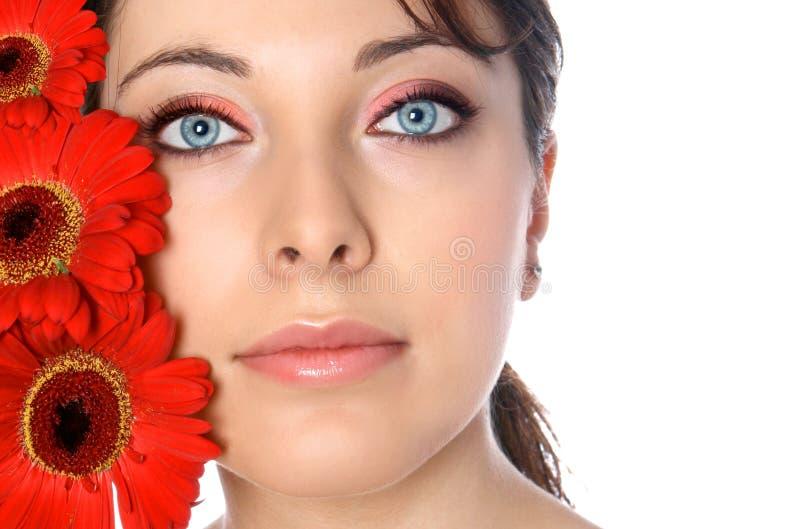 Vrouw met rode gerberas stock afbeelding
