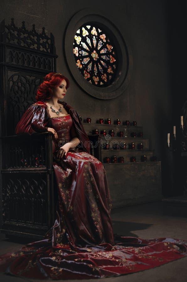 Vrouw met rode haarzitting op een troon stock foto's