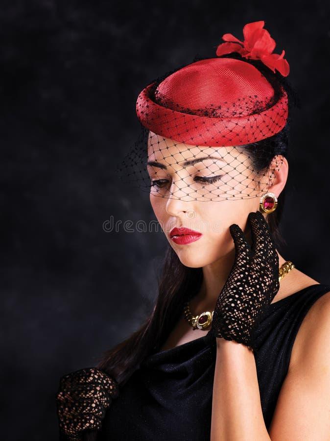 Vrouw met rode hoed en zwarte handschoenen stock foto's