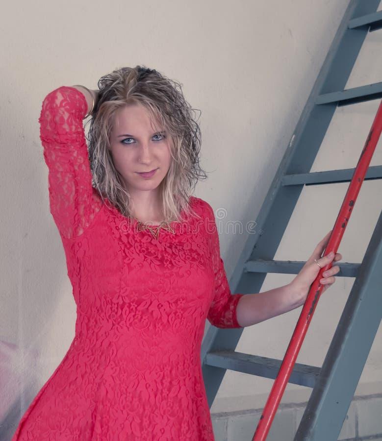 Vrouw met rode kleding op ladder stock afbeelding