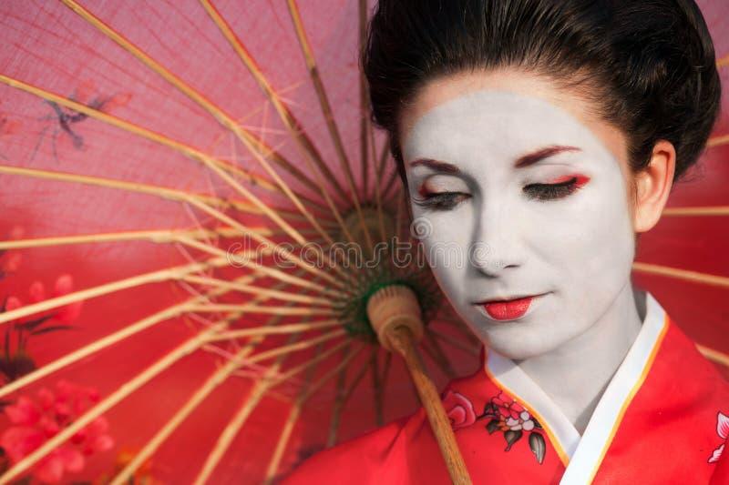 Vrouw met rode paraplu stock afbeelding