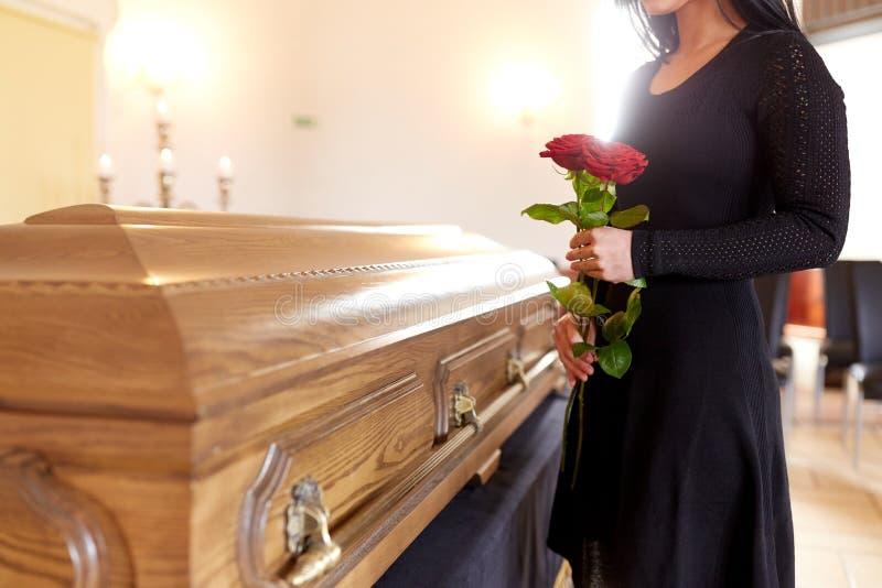 Vrouw met rode rozen en doodskist bij begrafenis stock afbeelding
