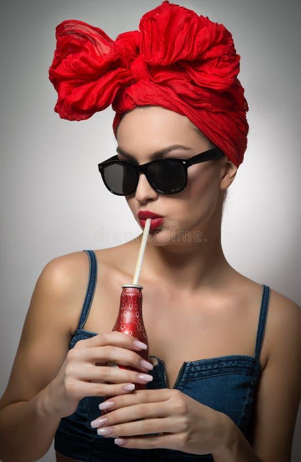 Vrouw met rode tulband en zonnebril die van een fles met een stro drinken Aantrekkelijk meisjesportret die een fles, studioschot  stock afbeeldingen