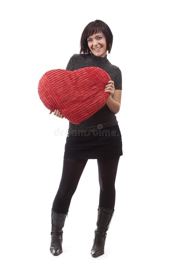 Vrouw met rood hart-vormig hoofdkussen stock foto