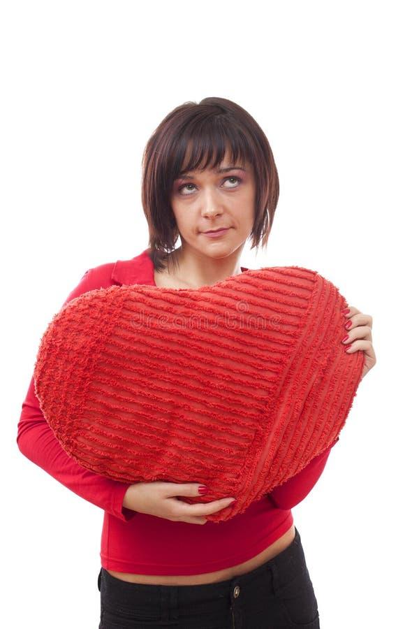 Vrouw met rood hart-vormig hoofdkussen stock fotografie