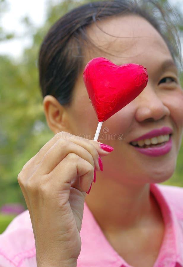 Vrouw met rood suikergoed stock fotografie