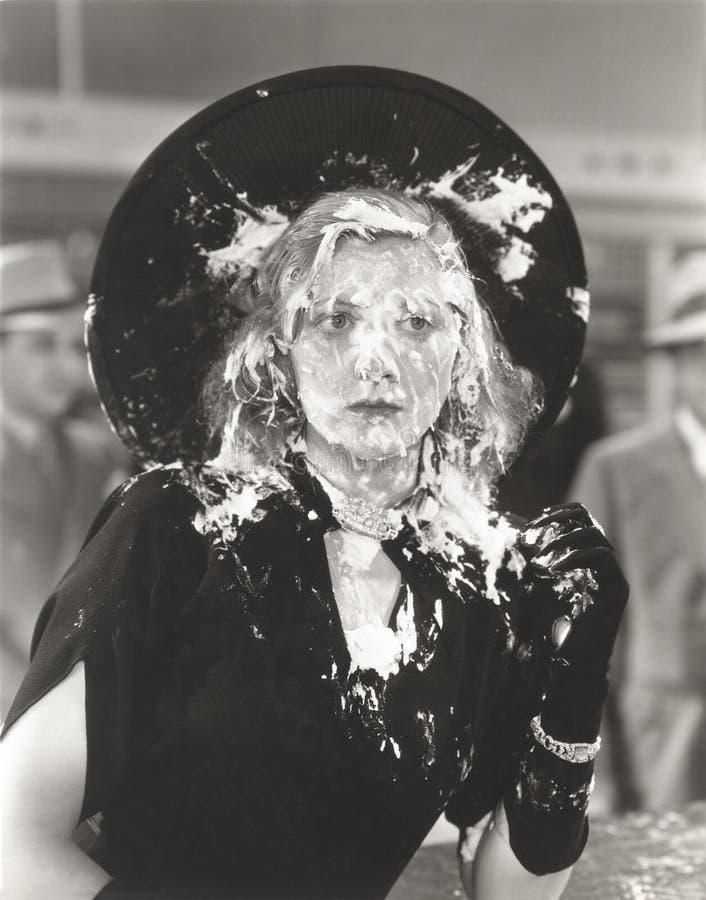 Vrouw met roompastei in haar gezicht wordt geworpen dat stock afbeeldingen