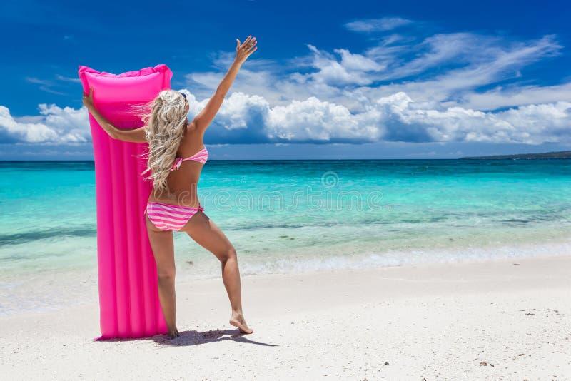 Vrouw met roze zwemmende matras op tropisch strand royalty-vrije stock afbeelding
