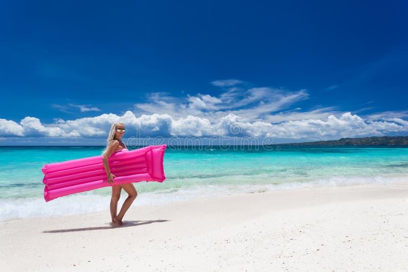 Vrouw met roze zwemmende matras op tropisch strand royalty-vrije stock afbeeldingen