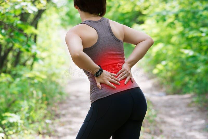 Vrouw met rugpijn, nierontsteking, verwonding tijdens training stock afbeelding